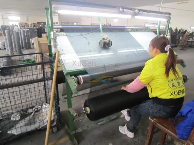 עובדת בסין מייצרת רשתות לחלונות במפעל
